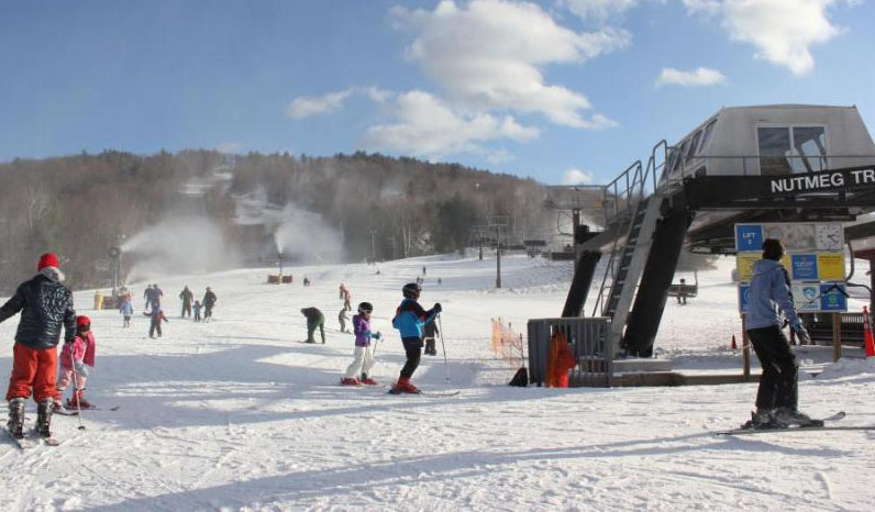 skiiers at base of Mohawk Mountain with hill in background and blue sky