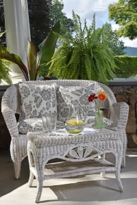 White wicker settee with floral pillow an fern in background