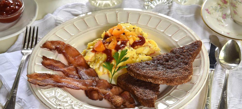 white plate with scrambled eggs with catsup and peppers bacon cinnamon toast jam and coffee