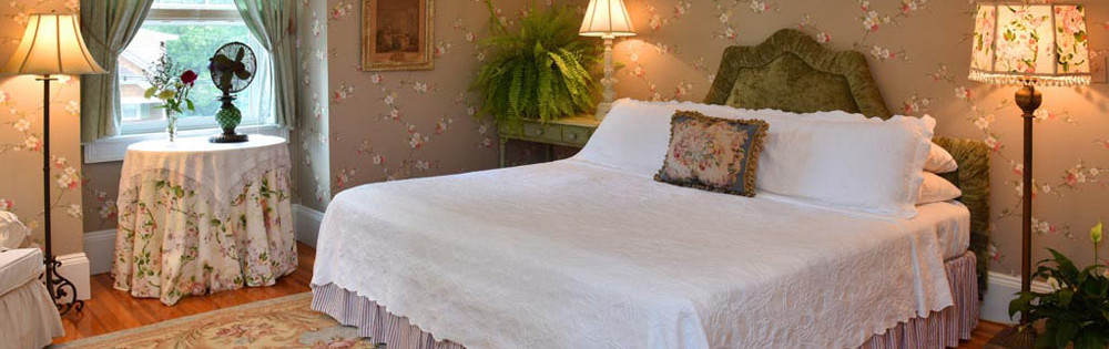 gray pink and white flowered walls white king bed green headboard and tan antique rug