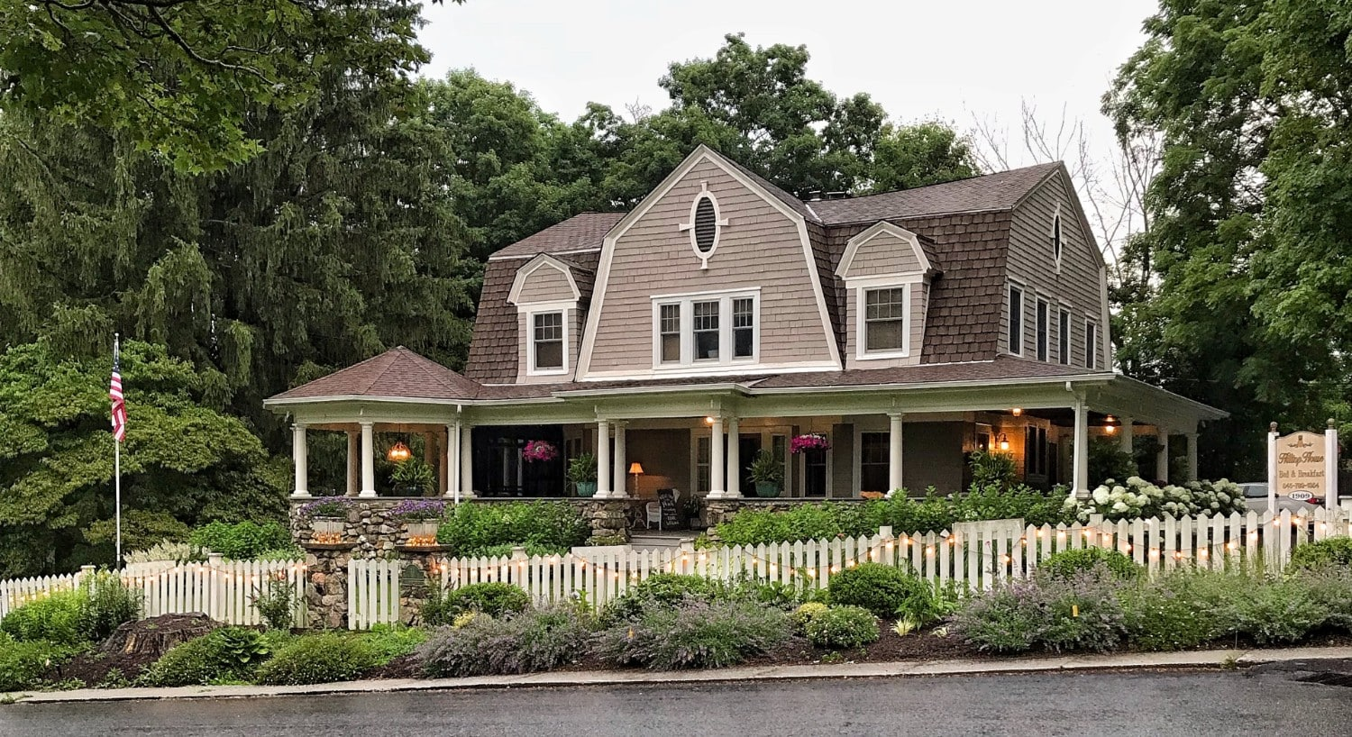 Front view from the street of large brown home with stone wrap around porch, white pillars, hanging plants and picket fence out front