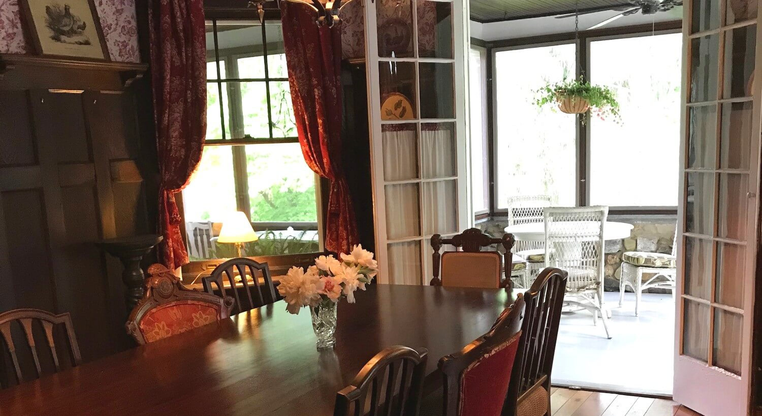 Dining room with dark brown table and hutch near window with red curtains and French doors opening to a bright patio