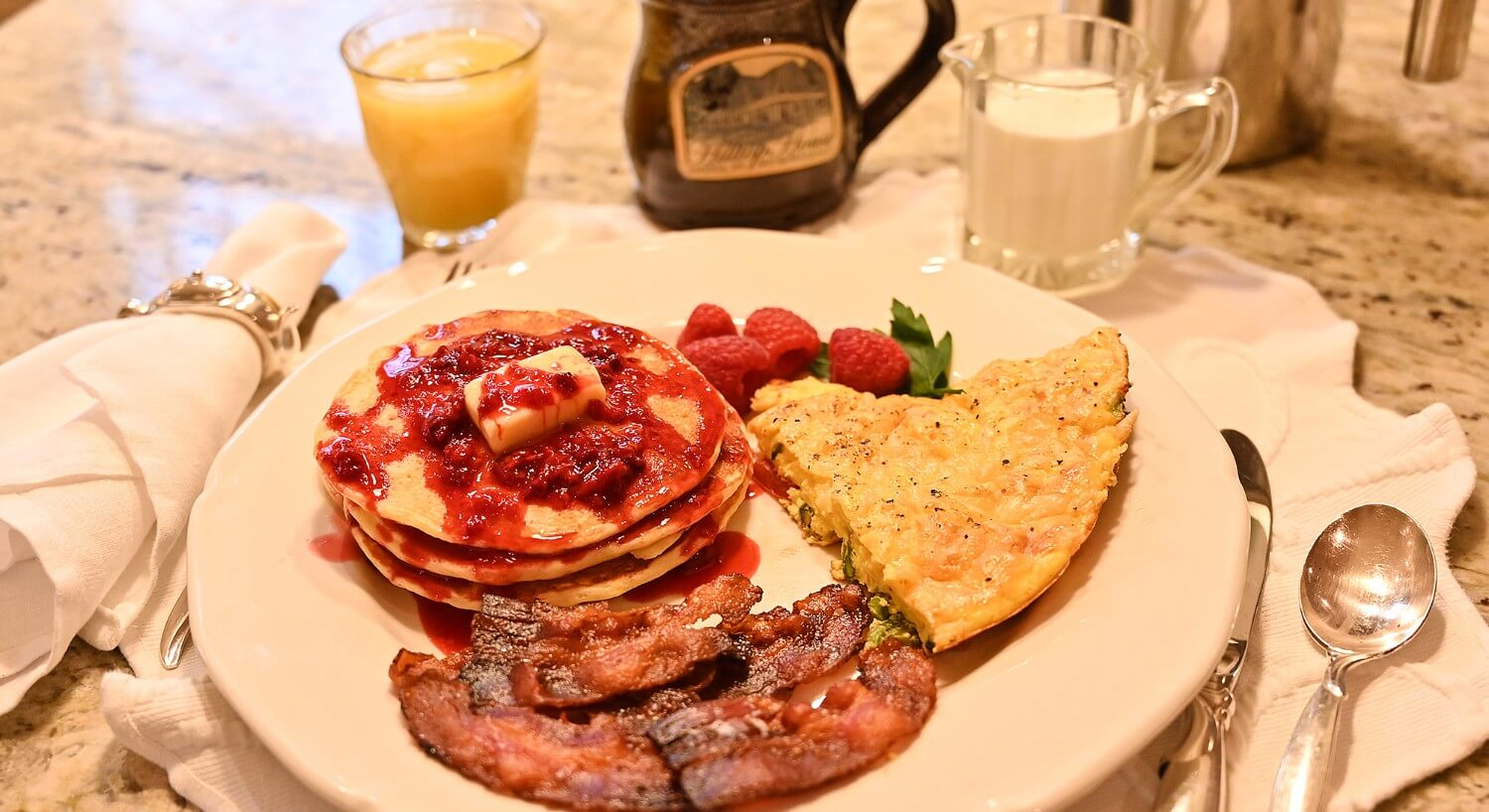 White breakfast plate showing pancakes with red berries, bacon and slice of egg quiche with raspberries