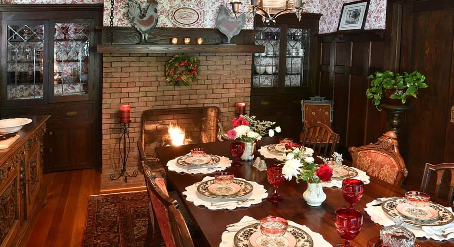 Large brown dining room table set with black and white china and red wine glasses next to a brick fireplace with fire lit