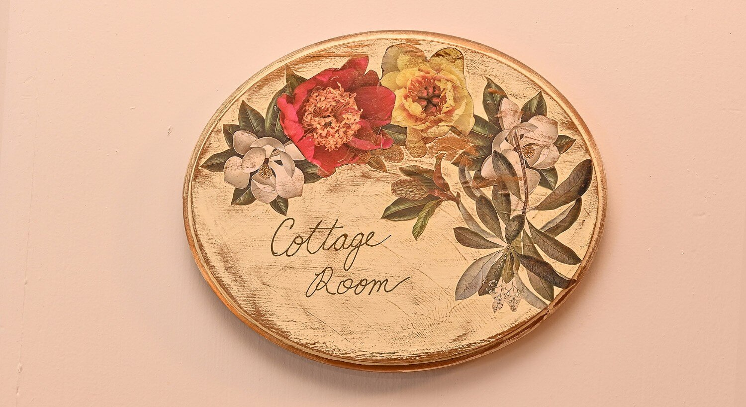 "Weathered cream oval sign with painted flowers and text ""cottage room"""