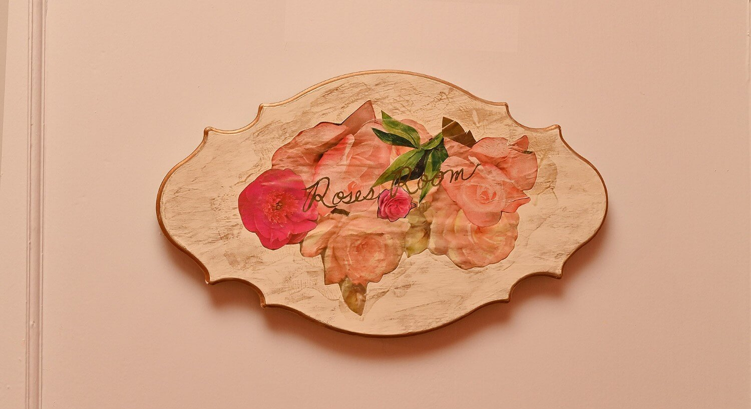 "Weathered cream oval sign with painted flowers and text ""roses room"""