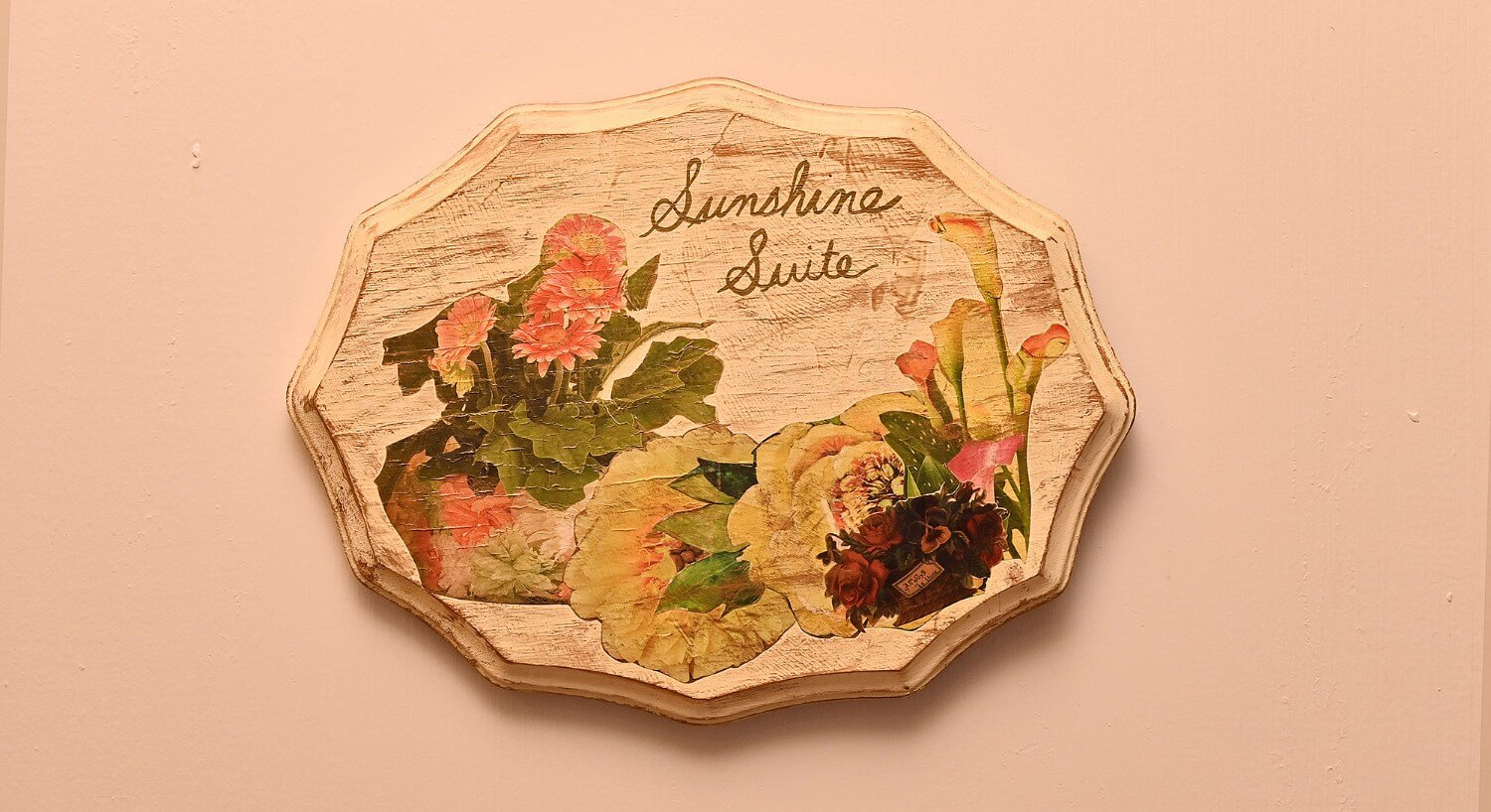 "Weathered cream oval sign with painted flowers and text ""sunshine suite"""