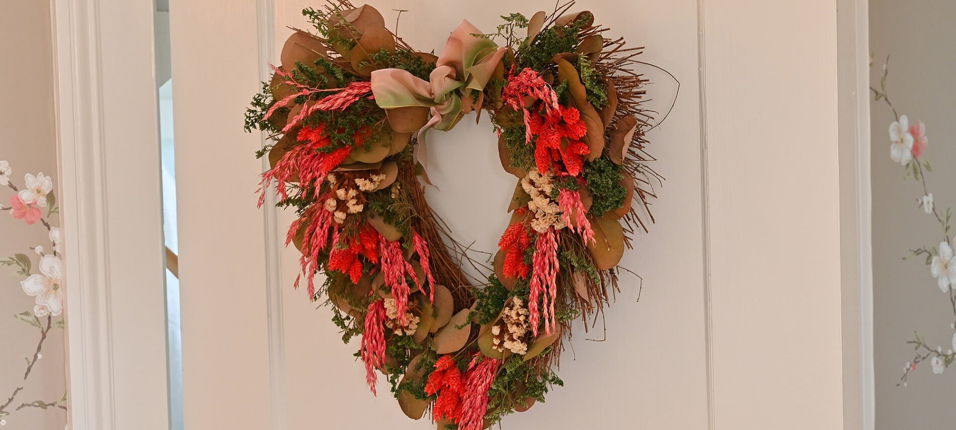 Wreath of red flowers and green leaves in the form of a heart hanging on a white door