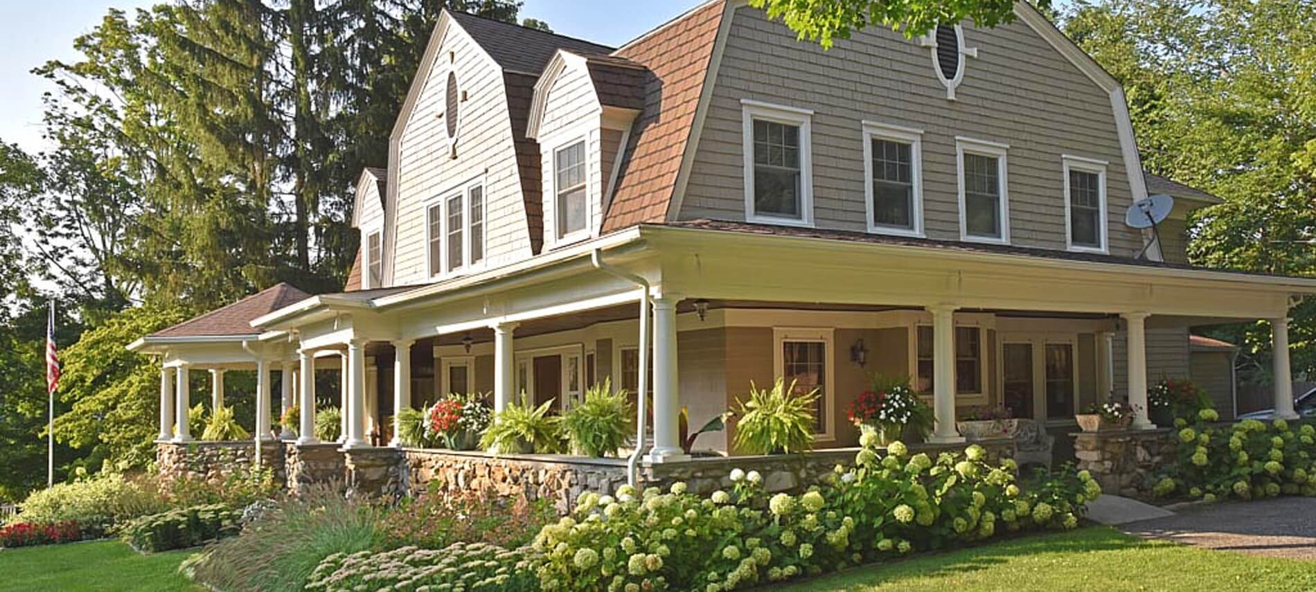 Bright sun shining on a large home with wrap around stone porch, white pillars and green landscaping