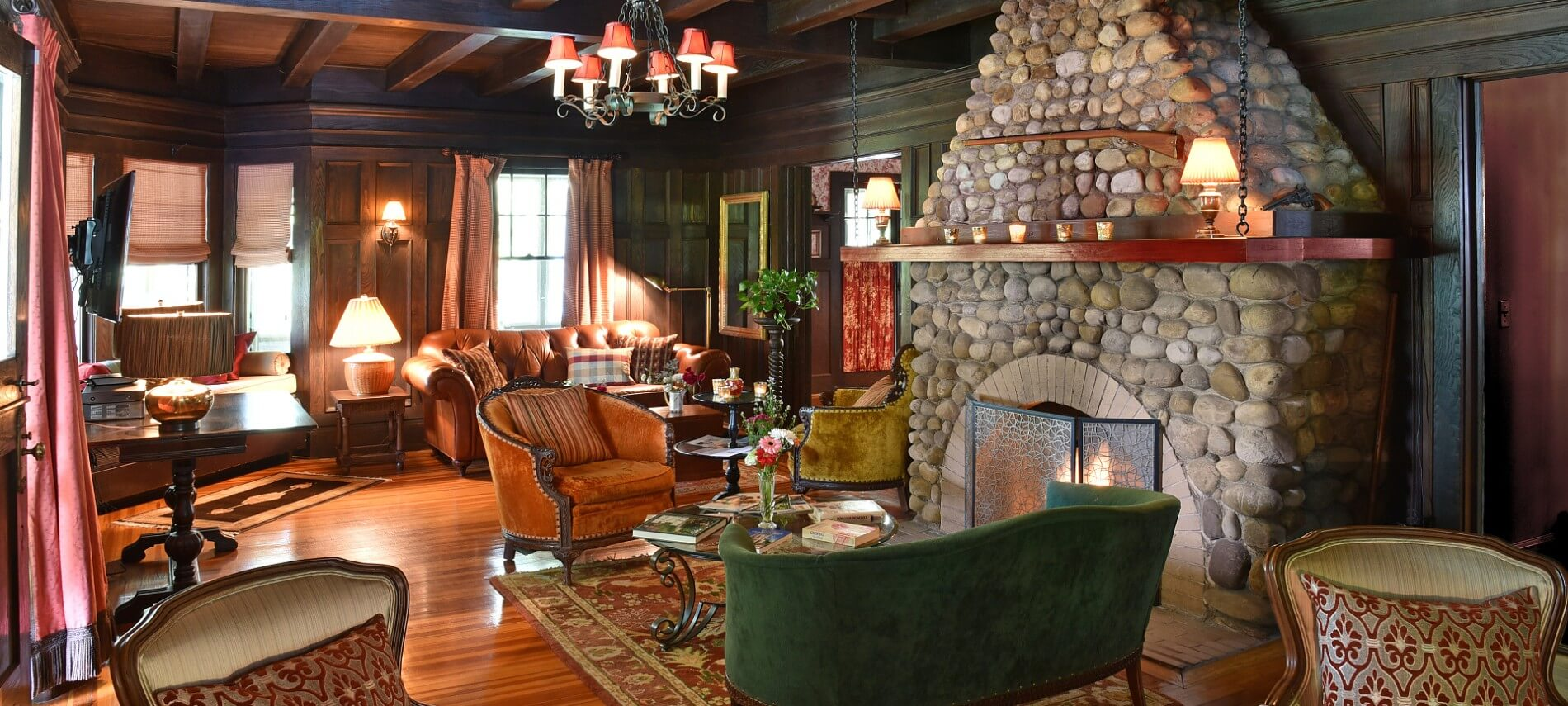 Cozy sitting room with tall rock fireplace, brown leather couch, two sitting chairs, square table and dark wood paneling on walls