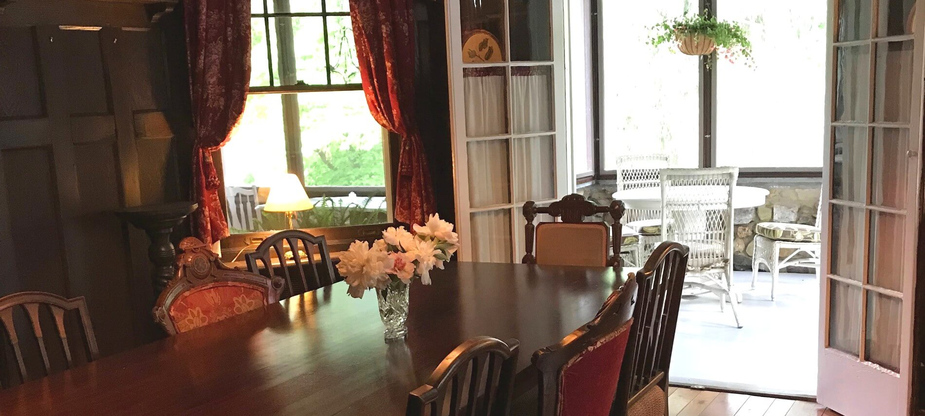 Elegant dining room with large dark brown table, red curtains and French doors opening to a bright patio
