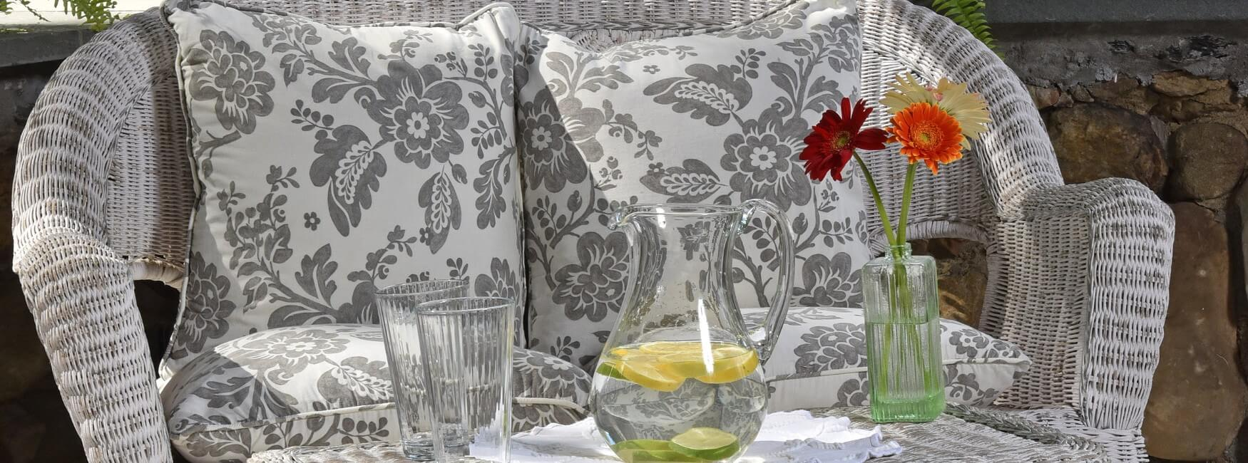 White wicker loveseat with flowered cushions with table holding pitcher of water, glasses and vase of flowers