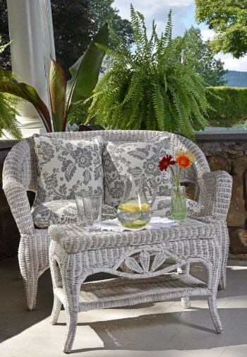 Corner of a stone porch featuring a white wicker love seat and table with green fern in background